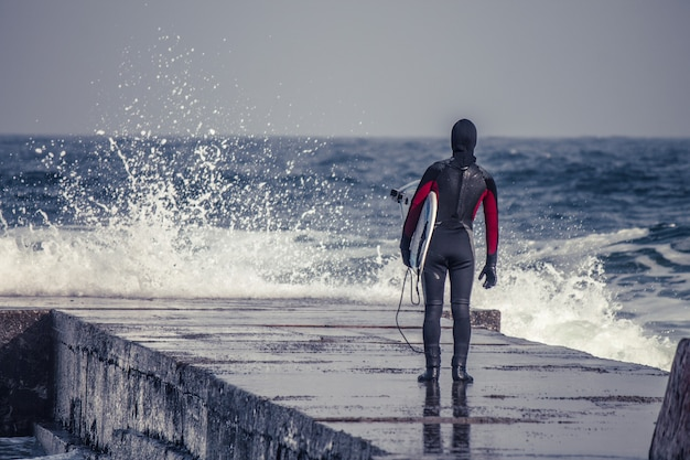 O surfista entra na água vestindo uma roupa de neoprene no inverno. surf frio. respingo da onda. terno impermeável