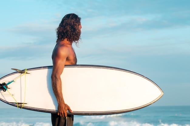O surfista está segurando uma prancha de surf na costa do oceano índico