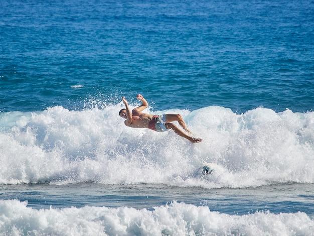 O surfista na onda apaga e cai da prancha de surf.