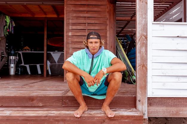 O surfista senta-se no terraço na praia