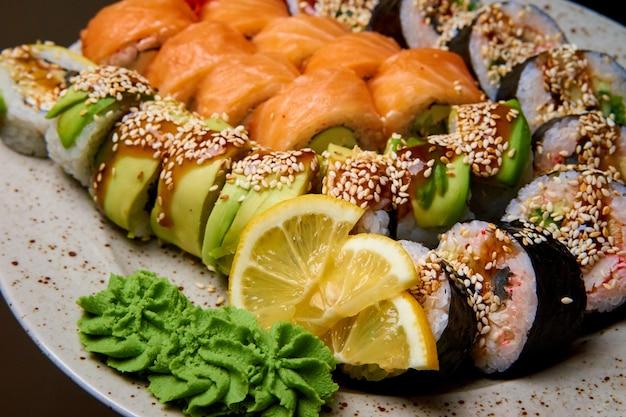 O sushi ajustou-se com wasabi e limão em uma placa.