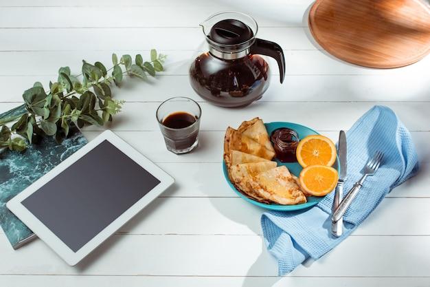 O tablet e panquecas com suco. café da manhã saudável