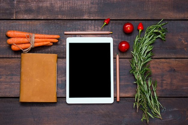 O tablet, notebook, pimentão fresco e amargo no fundo da mesa de madeira
