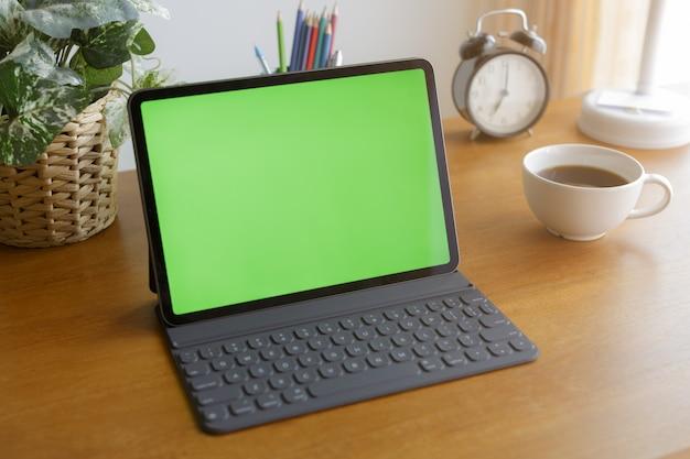 O tablet vazio tem uma tela verde em cima da mesa perto da janela.