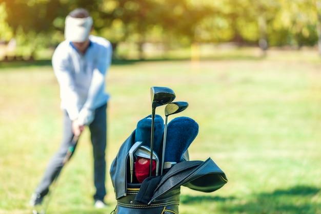 O taco de golfe é armazenado em um bolso com golfistas no gramado como o fundo desfocado.