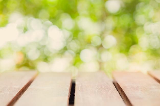 O tampo da mesa de madeira desfoca o fundo verde natural do jardim da manhã para produtos de montagem exibem layout de publicidade