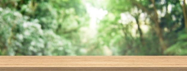 O tampo da mesa de madeira e a floresta verde do borrão para o tamanho da bandeira da montagem do produto e da exposição