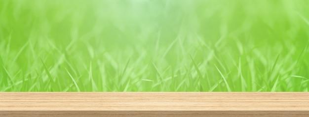 O tampo da mesa de madeira e a grama verde do borrão para o produto e o tamanho da bandeira da montagem da exposição.