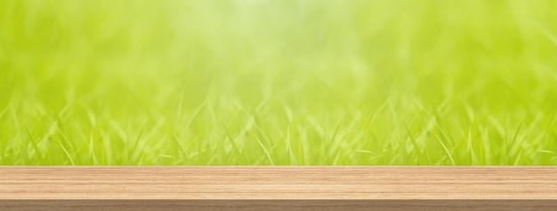 O tampo da mesa de madeira e a grama verde do borrão para o tamanho da bandeira da montagem do produto e da exposição