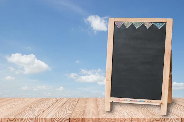 O tampo da mesa de madeira no céu azul com o quadro-negro vazio usado para indica seu produto.