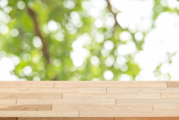 O tampo da mesa de madeira no fundo abstrato verde do borrão pode ser usado para a exposição ou a montagem seu p