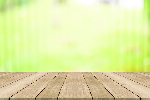 O tampo da mesa de madeira no fundo borrado verde da natureza, para a montagem seus produtos