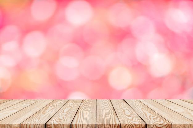 O tampo da mesa de madeira no fundo cor-de-rosa do borrão pode ser usado para a exposição ou a montagem seus produtos