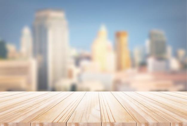 O tampo da mesa de madeira no fundo da paisagem da cidade da noite do borrão - pode ser usado para a exposição ou a montagem seus produtos