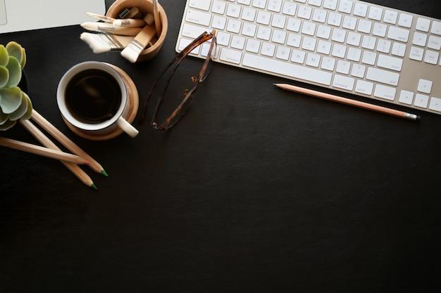O tampo da mesa escuro de couro da mesa do escritório com computador do teclado, materiais de escritório, vidros