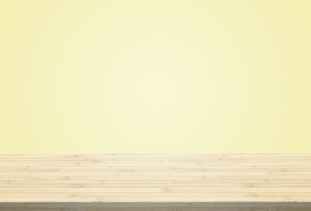 O tampo da mesa estratificado no fundo amarelo pálido pastel pode pôr ou montar seus produtos