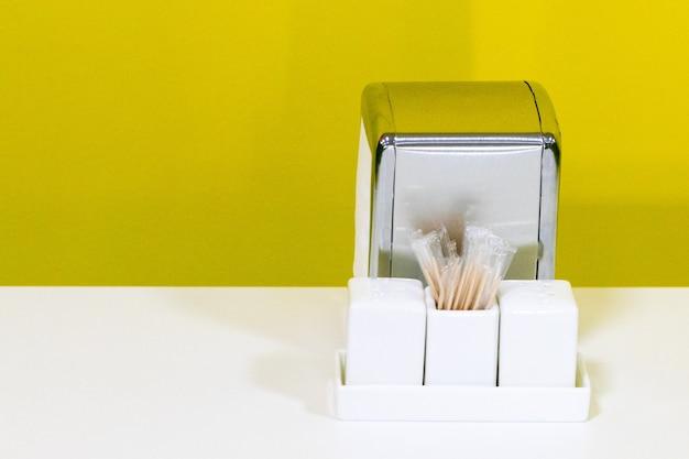 O tampo de uma mesa de restaurante ou café montado em um fundo branco com espaço de cópia inclui porta-guardanapos, saleiro e pimenteiro. conceito de serviço de alimentação.