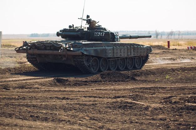 O tanque blindado monta em off-road. exercícios de tanque no campo.