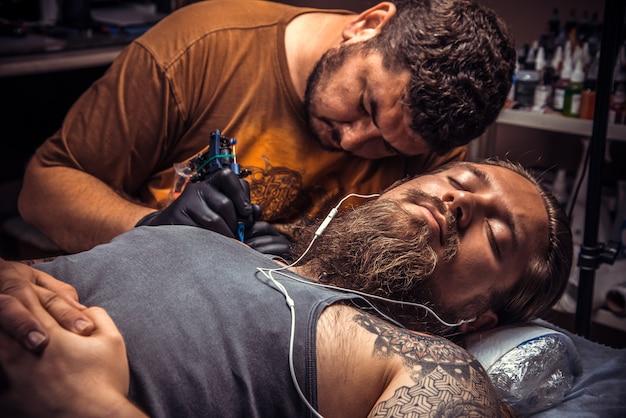 O tatuador profissional cria uma tatuagem em um estúdio de tatuagem.