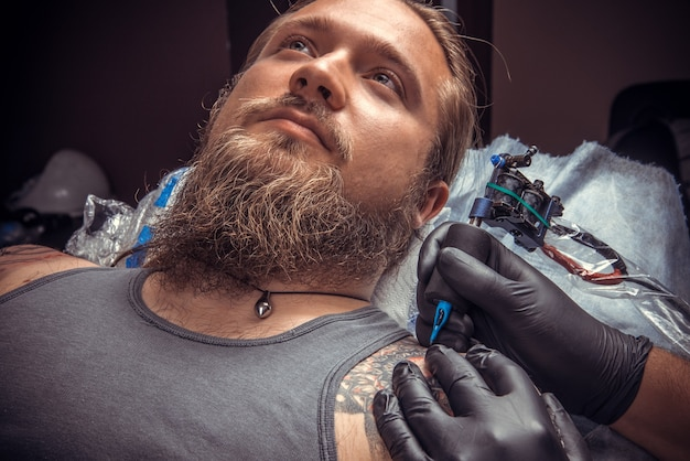 O tatuador profissional cria uma tatuagem no estúdio de tatuagem. homem usando luvas, posando no estúdio de tatuagem.