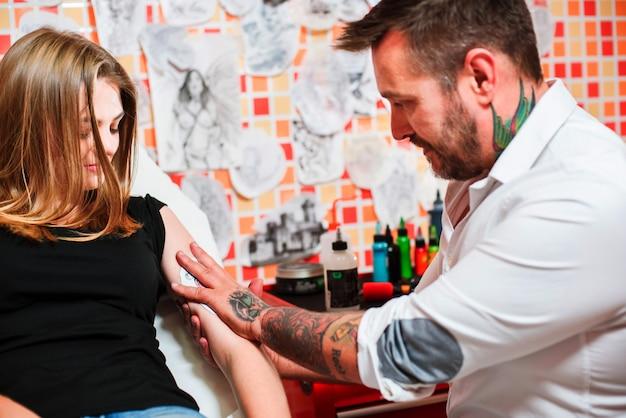 O tatuador profissional faz tatuagem