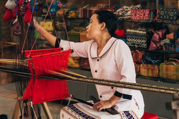 O tecelão fêmea trabalha atrás da máquina de tecelagem asiática tradicional do fio de seda
