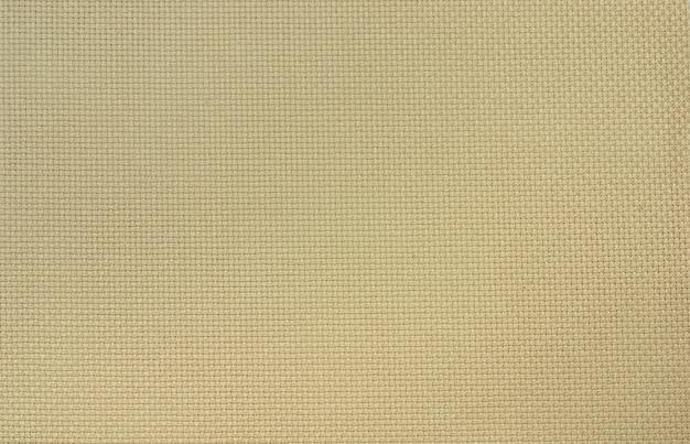O tecido de algodão aida bege de trama uniforme para ponto cruz. fundo.
