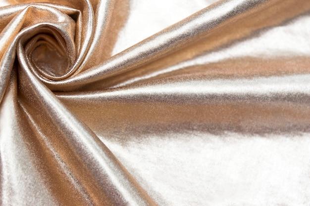 O tecido de parede dourado com pregas torcidas.