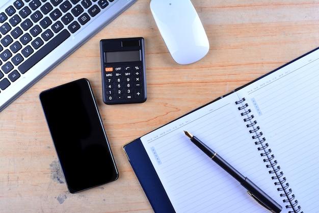 O teclado com mouse, caneta-tinteiro, notebook, calculadora e smartphone em uma mesa