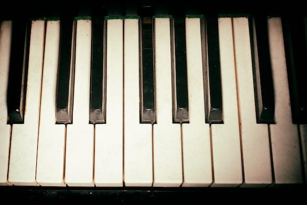 O teclado de piano antigo fecha-se como um fundo de música. com textura de papel com poeira e arranhões