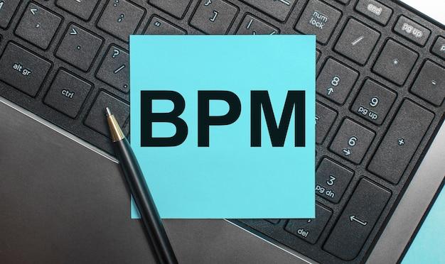 O teclado do computador possui uma caneta e um adesivo azul com o texto bpm business process management. postura plana.
