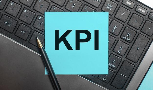 O teclado do computador possui uma caneta e um adesivo azul com o texto kpi. postura plana.