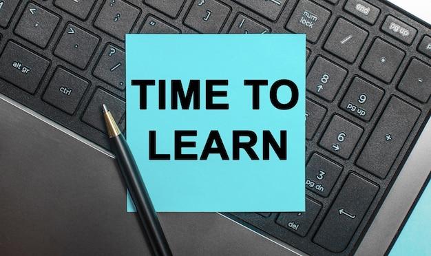 O teclado do computador tem uma caneta e um adesivo azul com o texto hora de aprender.