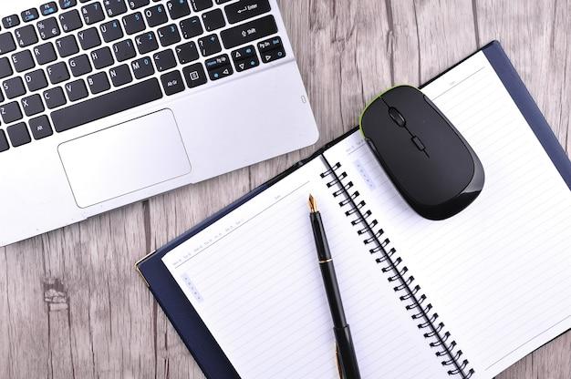 O teclado um mouse e acessórios de escritório em uma mesa