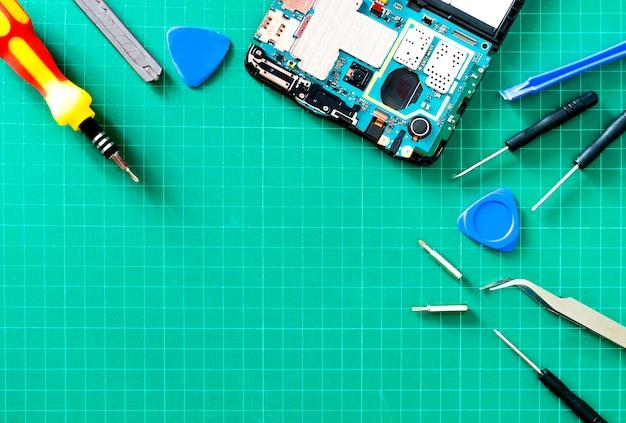 O técnico asiático consertando a placa-mãe do telefone inteligente no laboratório