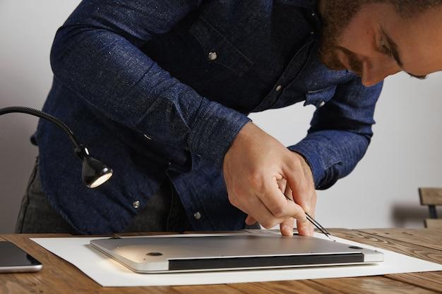 O técnico coloca pequenos parafusos no buraco com pinças anguladas para fechar a parte superior traseira do laptop do computador pessoal após o serviço de reparo e limpeza em seu laboratório