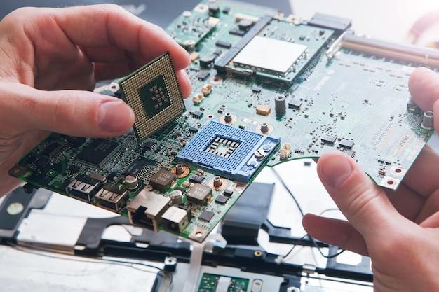 O técnico conecta o microprocessador da cpu ao soquete da placa-mãe. plano de fundo da oficina