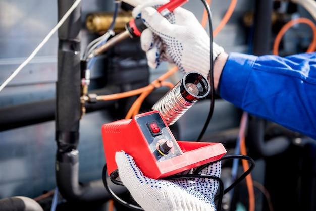 O técnico conserta sensores eletrônicos de temperatura com um ferro de solda eletrônico