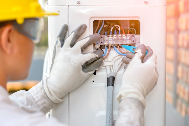 O técnico de ar condicionado está verificando o sistema do compressor de ar