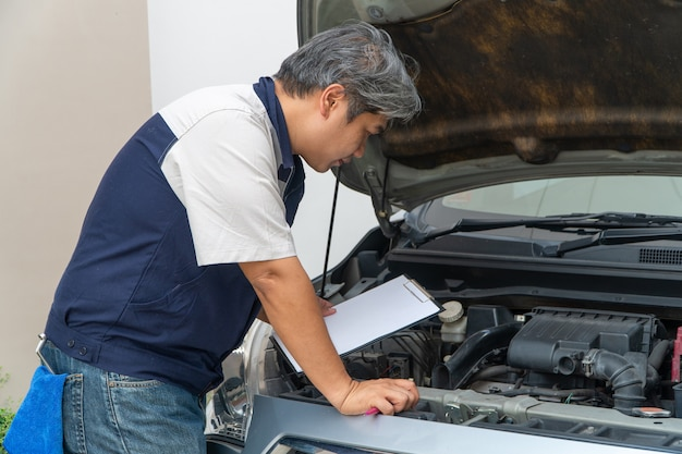 O técnico de automóveis verifica o motor e o sistema de arrefecimento antes de viajar de férias prolongadas.