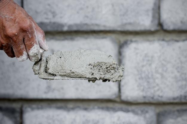 O técnico de cimento está criando a parede.
