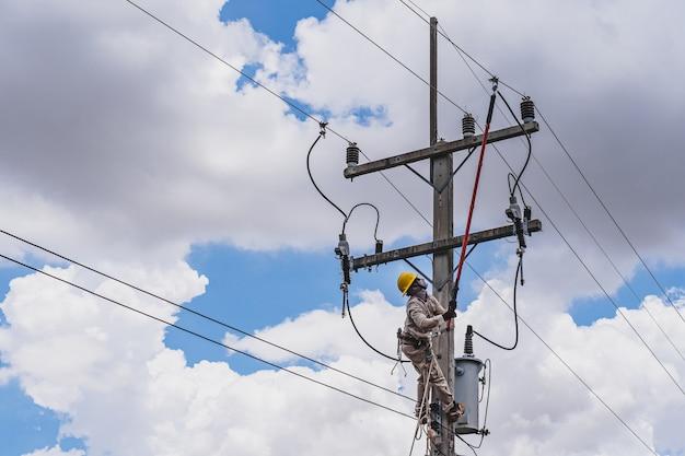 O técnico de linha de força usa uma braçadeira (ferramenta isolada) para fechar um transformador em linhas de energia elétrica de alta tensão energizadas.