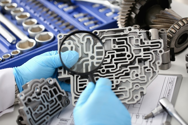 O técnico de manutenção automática para caixas de câmbio automáticas mantém as mãos em luvas de proteção azuis, examina através das lentes os detalhes da unidade hidráulica, realiza diagnósticos e estima os detalhes em detalhes.