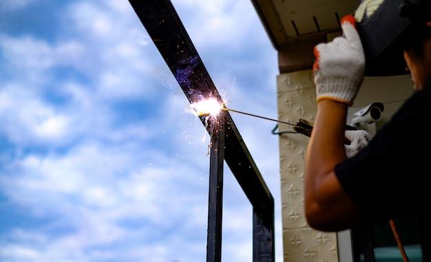O técnico de soldagem está soldando aço com faíscas voando