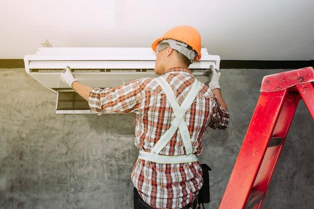 O técnico do ar condicionado está desmontando o ar condicionado para inspeção.