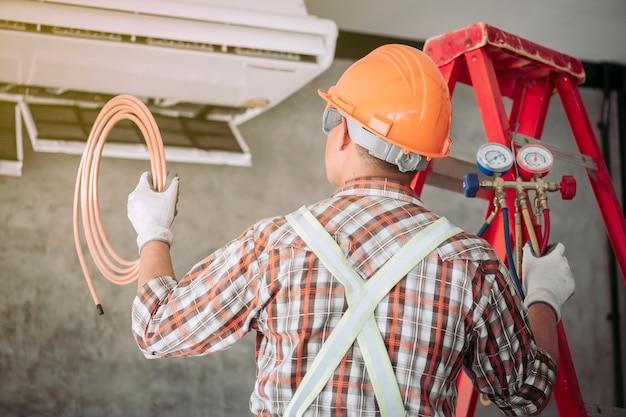 O técnico do ar condicionado está verificando e usando idéias para consertar o ar.