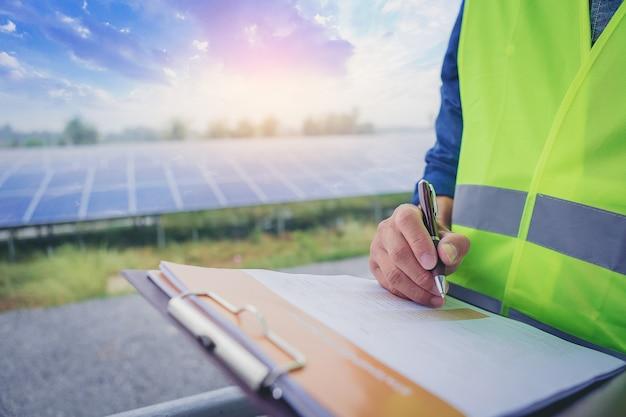 O técnico elétrico e o instrumento fazem uma nota estatística do sistema elétrico no campo do painel solar.