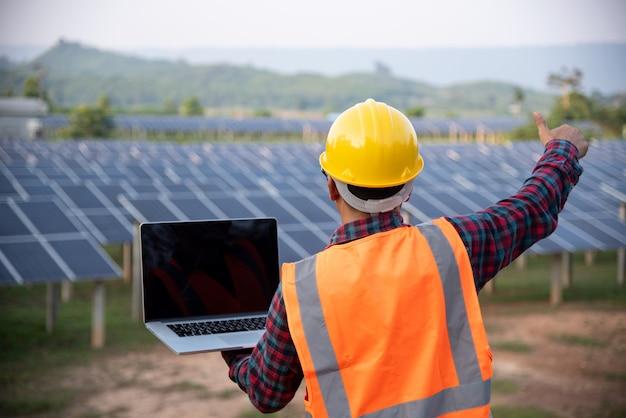 O técnico em engenharia de energia das células solares verifica a manutenção dos painéis solares.