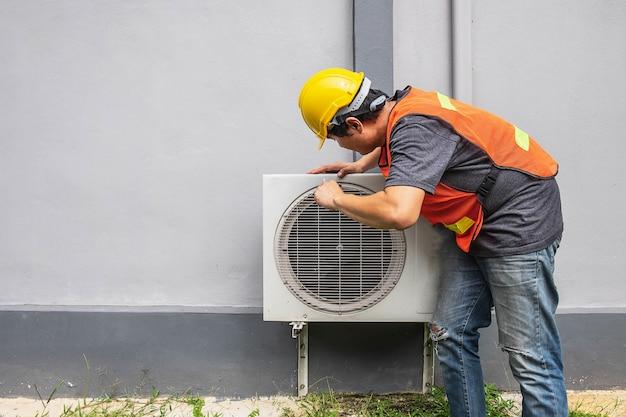 O técnico está consertando o ar condicionado.