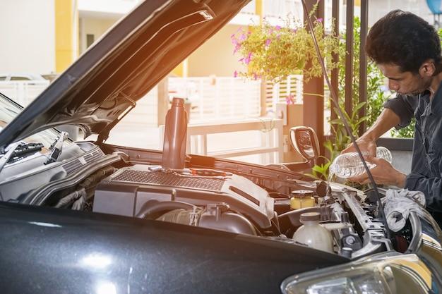 O técnico está derramando água limpa no radiador do carro.